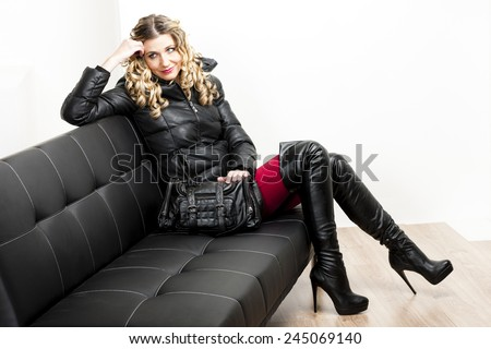 woman wearing fashionable clothes sitting with a handbag on a sofa - stock photo