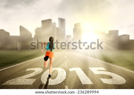 Woman wearing fitness clothes, running towards the future 2015 - stock photo