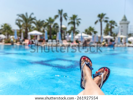 Woman wearing flip-flops laying on the sunbed near the pool - stock photo