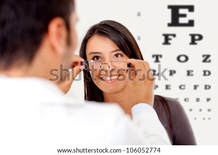Woman wearing glasses after taking a vision test at the doctor - stock photo