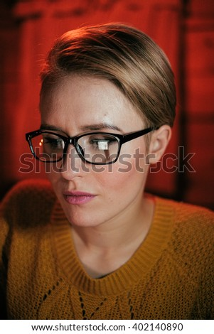 woman wearing glasses looking into computer screen at night, reflection of the screen in her glasses, artificial lightning