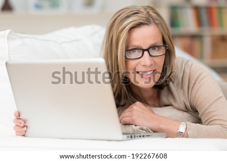 Woman wearing glasses working at home on her laptop computer recling on a sofa pausing to look at the camera with a quizzical expression ans small smile - stock photo