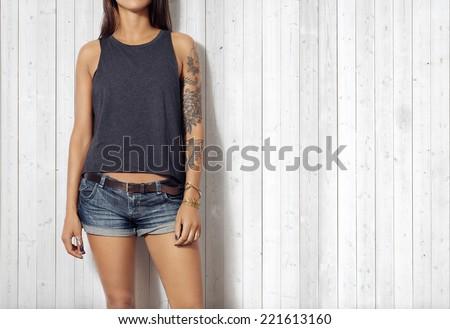 Woman wearing gray sleeveless t-shirt. Wood wall background. - stock photo