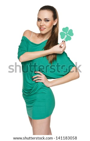 Woman wearing green dress showing artificial green shamrock leaf against white  background - stock photo