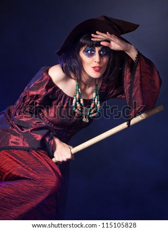woman wearing halloween witch  fly by broom - stock photo