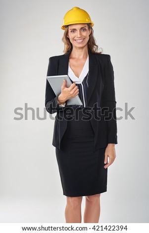 Woman wearing hardhat safety helmet holding tablet device, architect surveyor engineer professional - stock photo