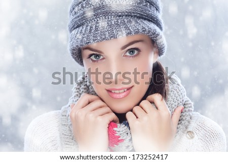 Woman wearing hat, enjoying outdoors while snowing.Studio shot.Winter atmosphere and falling snow added in post production.