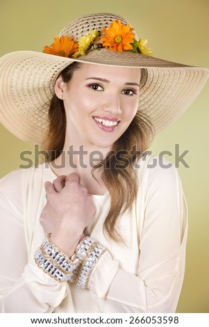 woman wearing hat with flowers on light green background