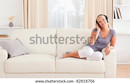Woman wearing headphones in her living room