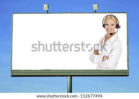 Woman wearing headset smiling to you from a big billboard - stock photo