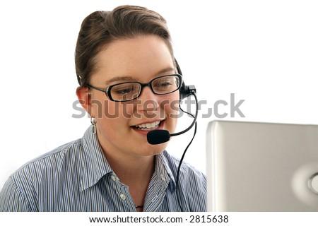 Woman wearing headset using a computer. - stock photo