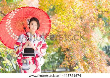 woman wearing japanese traditional kimono in autumn - stock photo