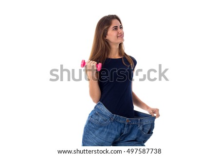 Woman wearing jeans of much bigger size and holding a dumbbell