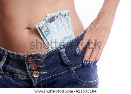 Woman wearing jeans shorts with Brazilian money at the waist on white background