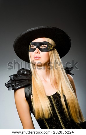 Woman wearing mask against dark background - stock photo