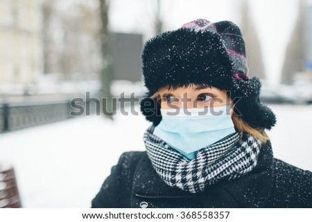 Woman wearing medical face mask in crowded city.  Female wearing face mask, protection from virus infection in winter time, feeling bad with headache