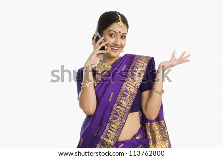 Woman wearing mekhla and talking on a mobile phone - stock photo