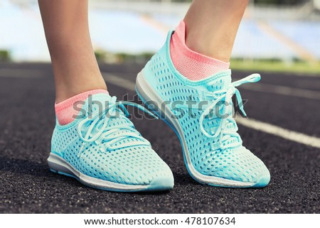 Woman wearing mint sneakers on a running stadium