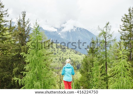 Woman wearing outdoor clothing (hardshell waterproof jacket and softshell pants), standing with trekking poles in hands and preparing for hiking in Bavarian Alps - exploring and adventure concept - stock photo