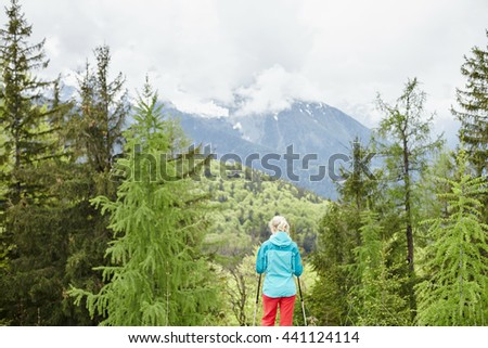 Woman wearing outdoor clothing (hardshell waterproof jacket and softshell pants) standing with trekking poles in hands and preparing for hiking tour in Bavarian Alps - exploring and adventure concept - stock photo
