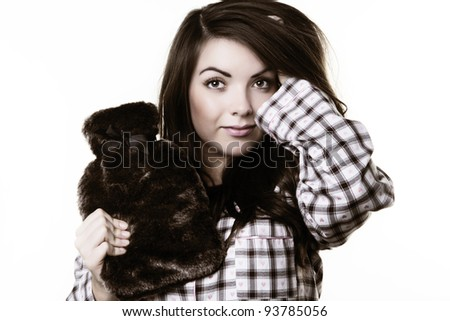 woman wearing pajamas and holding a nice  hot water bottle getting ready to go to bed. Please note this image has had a half colour and black and white with a sepia toning effect added. - stock photo