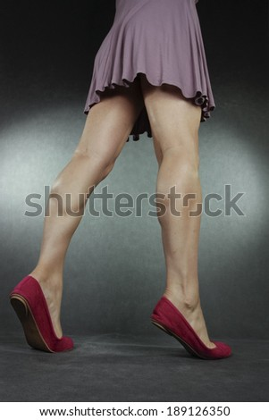 Woman wearing pink dress and red high heels over grey background - stock photo