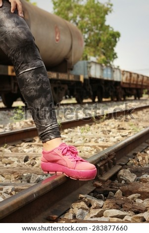 Woman wearing pink shoes at train station.