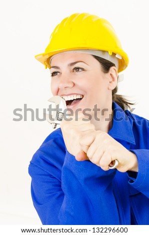 Woman wearing protective equipment holding adjustable wrench - stock photo