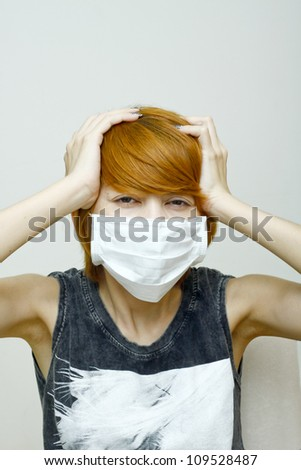 Woman wearing protective mask,Woman with headache holding her hands to the head.