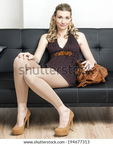 woman wearing pumps with a handbag sitting on sofa