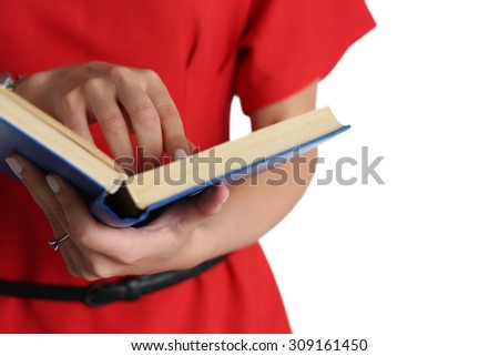 Woman wearing red dress holding blue book and pointing in it with finger isolated on white background. Female hands holding textbook closeup. Education, studying, learning, teaching, bookshop concept - stock photo