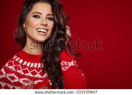Woman wearing red sweater against red wall background