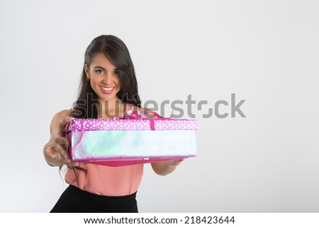 Woman wearing rosewood blouse and black skirt, with a  gift box on her hands