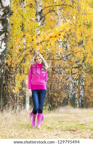 woman wearing rubber boots in autumnal nature - stock photo