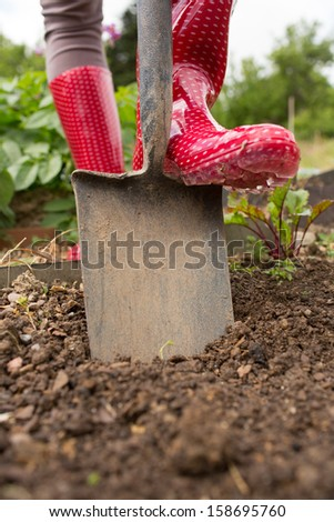 Woman wearing rubber boots using shovel in her garden - stock photo
