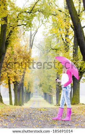 woman wearing rubber boots with umbrella in autumnal alley