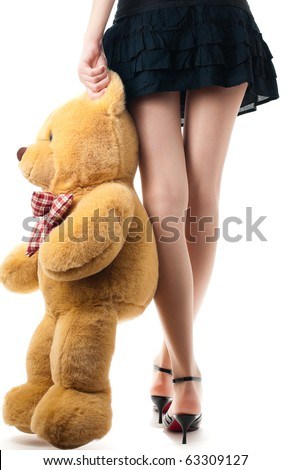 woman wearing skirt and high heels, holding toy bear near her legs, view of the back lower body part, isolated on white background - stock photo