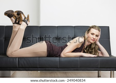 woman wearing summer shoes lying on sofa - stock photo