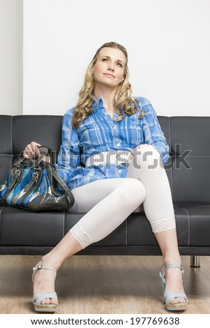 woman wearing summer shoes with a handbag sitting on sofa - stock photo