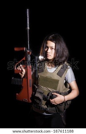 Woman wearing Tactical Gear and Holding a brown Steyr AUG A1 Gun. Isolated on black background. - stock photo