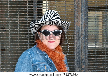 Woman wearing unusual clothing and fancy hat - stock photo