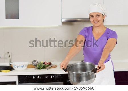 Woman wearing waist apron carrying cooking pot with both hands smiling - stock photo