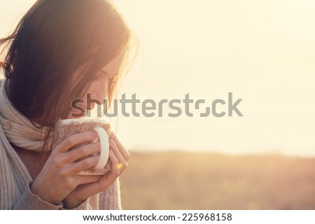 Woman wearing warm knit clothes drinking cup of hot tea or coffee outdoors in sunlight - stock photo