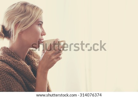 Woman wearing warm knitted sweater is drinking cup of hot tea or coffee near window in autumn morning sunlight, photo warm toned - stock photo
