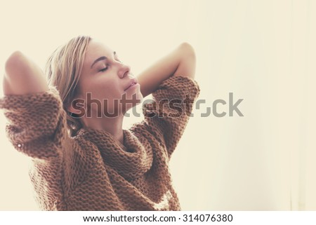 Woman wearing warm knitted sweater is relaxing window in autumn morning sunlight, photo warm toned - stock photo