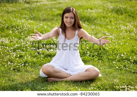 woman wearing white dress sitting on grass in park - stock photo
