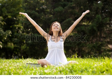 woman wearing white dress sitting on grass in park with netbook