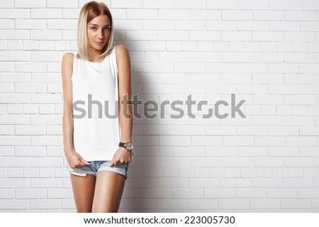 woman wearing white t-shirt against brick wall - stock photo