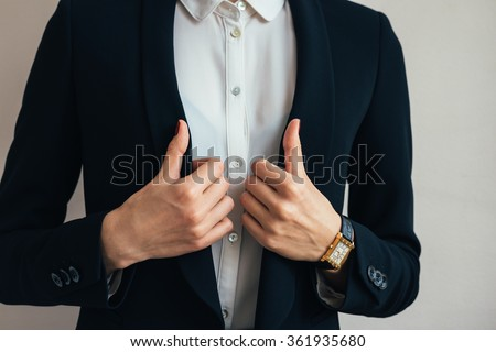 Woman wears a business suit jacket. In her hand wristwatch. Close-up of a woman in a business suit and wristwatch. - stock photo