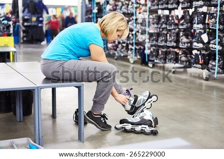 Woman wears roller skates in the sports shop - stock photo